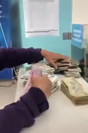 Cô bán rau đi đổi tiền lẻ thành tiền chẵn đóng học cho con