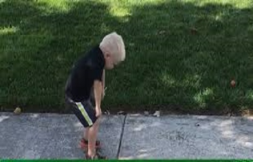 Cậu bé hài hước nhảy múa theo hình nộm bơm hơi bên đường
